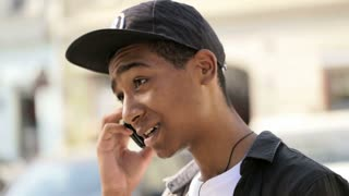 Happy teenager is hapily talking on his mobile phone
