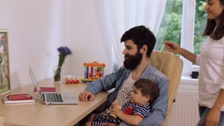 Happy young couple with son using laptop at desk, young woman kissing bearded man