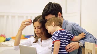 Happy young family with baby boy using tablet computer at modern home for playing games and education