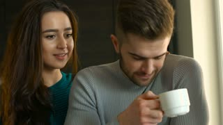 Happy young smiling couple relaxing at home, man drinking coffee and woman talk to him at home.