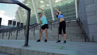 Healthy fitness woman and handsome sporty man on stadium warming up on stairs