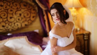 Incredibly beautiful bride wearing beautiful fashionable white wedding dress posing on a professional camera and smile .