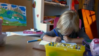 Kid with blond hairs painting and drawing on paper sitting at table, close-up