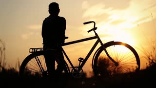 Little boy riding his bicycle and enjoying the beauty of sundown.