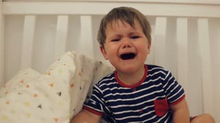 Little cute boy wearing blue striped pijama crying in the bed