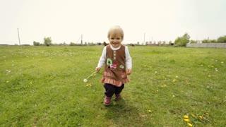 Little funny girl holding dandelion in her hand running on the grass.