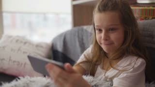 Little girl having fun with game in smartphone