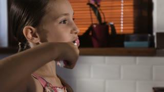 Little girl in pink pyjamas in bathroom brushing teeth, close-up