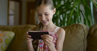 Little girl playing games or using app on tablet sitting on white coach in living room. Beautiful kid girl sitting on cozy white home sofa and looking at smartphone screen