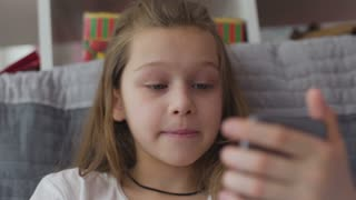 Little serisously girl sitting with smartphone