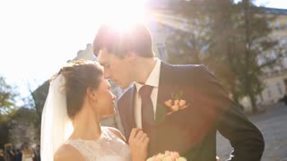 luxury romantic happy bride and groom celebrating marriage on the background of old sunny city  shot in slow motion  close up