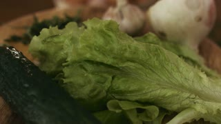 Macro footage of vegetables spinning around on a wooden plate in the kitchen including onion, garlic, lettuce, arucula, cucumber