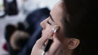 Make-up artist applying white eyeshadow in the corner of model's  eye and holding a shell with eyeshadow on background, close up