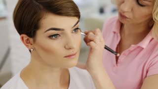 Makeup artist applying powder with make up brush to beautiful brunette woman with short haircut, close-up