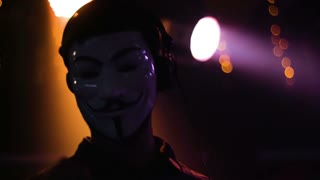 Male DJ worn anonymous mask  and big headphones playing music at the party, turning knobs on his control desk.