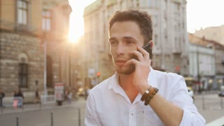Male in his 20s have a serious talk on phone and then reacting with a wide smile.