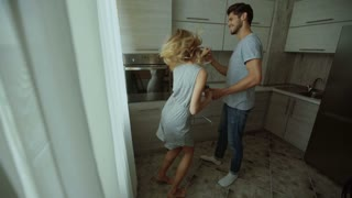 Man and woman dancing in the kitchen at home