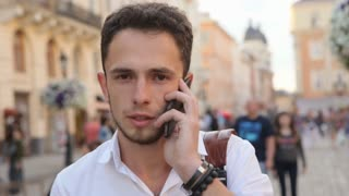 Man have conversation on phone outdoors in slow motion. Student talking on cellphone in the middle of european city.