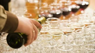 Man pouring wine into glasses at a party