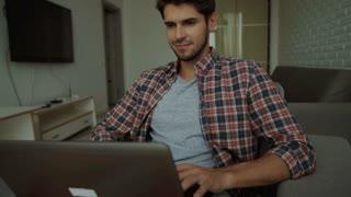 Man typing on a laptop, woman watching him.
