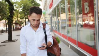 Man typing on telephone in the middle of a street. Young handsome guy texting on smartphone.