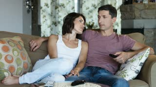 Married couple relaxing watching tv at home on the couch with embrace and cuddle