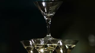 Martini glasses in the form of a cascade or pyramid lit light at the party