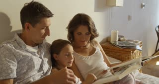 Mother, father and daughter wearing pajamas reading a book together laying in bed