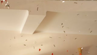 Multicolored confetti falling on white wall. Conception of celebration and party