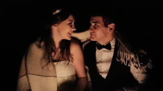 Nature lovers, bride and groom on sitting around the campfire at night in their wedding day