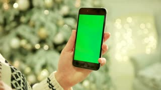 NEW YORK - January 17, 2015: Close-up of female hands touching green screen on mobile phone. Chroma Key. Close up. Tracking motion. Vertical. with blur christmas decoration background