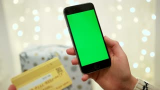 NEW YORK - January 17, 2015: Hands holding credit card and using mobile smart phone Online shopping. Chroma Key. Close up. Tracking motion. with blur christmas decoration background