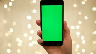 NEW YORK - January 17, 2015: Woman hand hold smart phone on abstract blurred bokeh of light background background. . Green screen Chroma Key. Close up. Tracking motion. Vertical