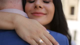 Newlyweds are hugging near old brown wall, bride is dressed in lace white wedding dress and veil, groom wearing blue suit stands back