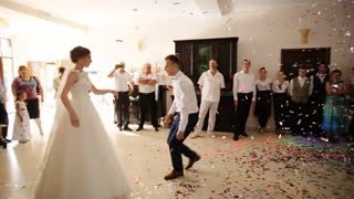 Newlyweds spinning at wedding dance to the applause of a large group of people