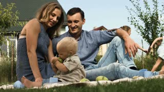 Outdoor group portrait of happy family having picnic on green grass in garden and enjoying happy moment