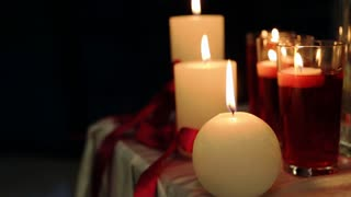 Peaceful valentine candles light for dinner on table decorated with tablecloth and red tapes at night