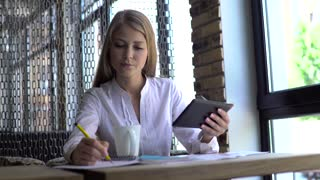 People, technology and lifestyle concept - smiling young woman in eyeglasses with tablet pc computer and notebook taking notes at café