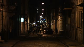 People walking by a street of an old traditional town at night. Establishing shot.