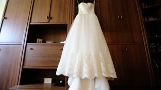 Perfect white wedding dress on hanger and fashionable shoes in the room of the bride.