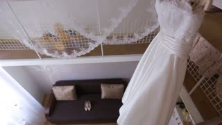 Perfect white wedding dress on hanger and fashionable shoes in the room of the bride
