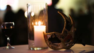 Picture of a firing candle in glass cup, a glass of red wine and a carnival mask left on a table in a club, people dancing on a background.