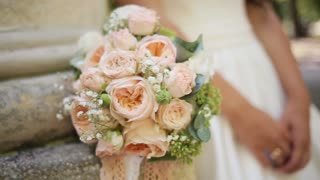 Pink and white wedding bouquet of roses and hands of the bride with wedding ring