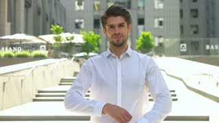 Portrait of a smiling handsome businessman in white shirt with arms folded standing near modern business center