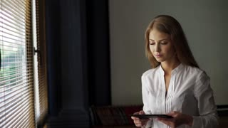 Portrait of a young beautiful blonde women reading electronic book on her digital tablet while standing near big window in office space