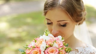 Portrait of beautiful bride with bouquet over green nature background, smiley face of happy woman, head and shoulder female portrait