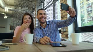 Portrait of lovely couple having fun and grimacing while taking selfie using mobile phone . Two happy young people spending time together at a cafe