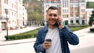 Portrait of stylish handsome young man with bristle standing outdoors.  Smiling man talking on mobile phone and holding cup of coffee