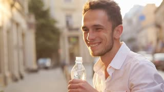 Positive handsome thirsty man in his 20s drinking water from the bottle.