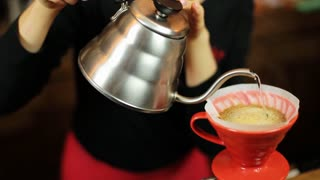 Pour over coffee brewing method whole process by barista girl. Barista girl pours water into the filter.